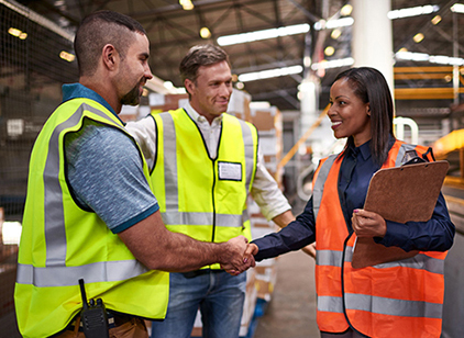 Two men and women talking in safety vests in factory